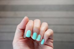 Close Up Green Manicure Nail. Beautiful Female's Hand Nails Polish on the Wood Floor Background Stock Photo