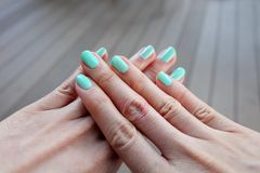 Close Up Green Manicure Nail. Beautiful Female's Hand Nails Polish on the Wood Floor Background Royalty Free Stock Images