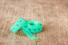 Close up green measuring tape on wooden table Royalty Free Stock Images