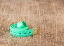 Close up green measuring tape on wooden table Royalty Free Stock Image