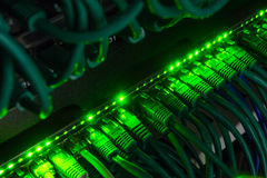 Close up of green network cables connected to switch glowing in the dark Stock Photos