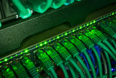 Close up of green network cables connected to switch glowing in the dark Stock Photo