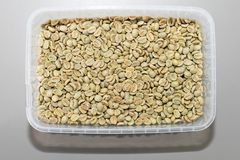 Arabica coffee beans. Close-up green no roasted Arabica coffee beans in container, texture, background Stock Images