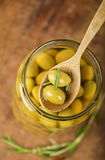 Close up green olives in bank,  rosemary Stock Images