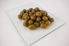 Close up of green olives on glass slab Stock Image
