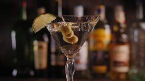 Close-up of a Martini glass with olives and lemon slowly rotating on the bar.