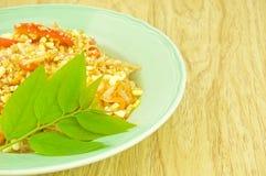 Close up green papaya salad with leaves of gooseberry. Close up green papaya salad or som tam with leaves of gooseberry on wood background Stock Image
