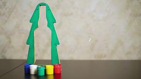Close-up green paper Christmas tree with cutout inside outline of bottle. And multicolored jars with gouache on table. Soap bubbles fall nearby stock video footage