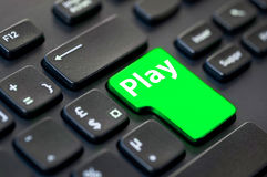 Close up of a green return key with the word play on computer Stock Image