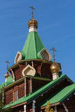 Close-up of green roofs and domes of wooden church on the blue s Stock Photos