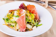 Close up Green Salad with prosciutto and pears in white plate close up. Served restaurant table. Selective focus, copy space.  stock photo