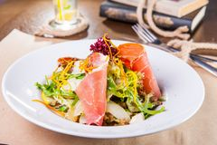 Close up Green Salad with prosciutto and pears in white plate close up. Served restaurant table. Selective focus, copy space royalty free stock photography