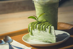 Close up green tea cake and matcha iced green tea on wooden salver. Close up green tea cake and matcha iced green tea on wooden salver with sunlight background royalty free stock photo