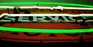 Close up of a green and white neon tubes on a sign. With an orange background Royalty Free Stock Photos