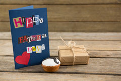 Close up of greeting card by gift and cupcake royalty free stock photos