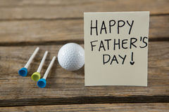 Close up of greeting card with happy fathers day text by golf ball and tees stock image
