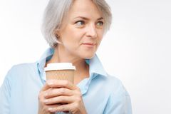 Close up of grey-haired woman holding cup of coffee Royalty Free Stock Images