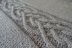 Close-up of grey handmade knit fabric with plait pattern Stock Image