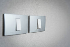 Close up grey light switches on texture background. Royalty Free Stock Image