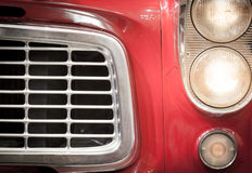 Close Up of Grille and Headlights of Red Vehicle Stock Images