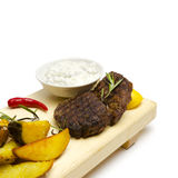 Close-up of grilled beef medallion served with roasted potato on the white background royalty free stock photo
