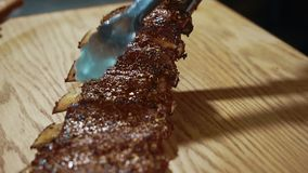 Close up of grilled beef ribs being put to the wooden cutting board in expensive restaurant, slow motion. stock video