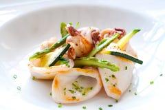 Close up of grilled calamari. Macro Close up of grilled calamari and green asparagus Stock Photography