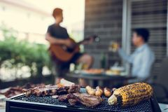 Close up grilled meats and various food on the grill and celebrations of friends who are playing guitar and sing together in their. Home royalty free stock photos