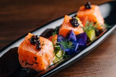 Close up Grilled Medium Rare Salmon Cube topping with caviar and served with strawberry and orange in black plate.  royalty free stock image