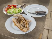 Close up grilled pork brisket slices, green salade and tomatoes royalty free stock images