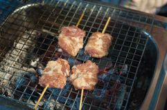 Close up Grilled Pork stick cooking night market, Thai cuisine traditional signature street food, quick and easy eating. Close up Grilled Pork stick cooking Royalty Free Stock Photo