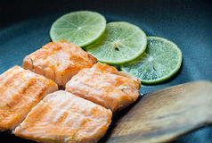 Close up grilled salmon steak on black pan with 3 lemon slices. royalty free stock images