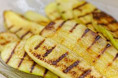 Close up grilled zucchini on plate. Macro of a vegetable. Shallow depth a field. stock images
