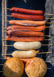 Close up Grilling Sausages and Bread on Sticks Stock Photo