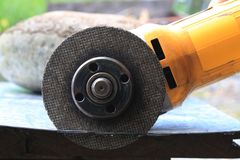 Close up of a grinder that has cut through a tin plate royalty free stock image