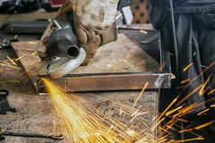 Close up grinds a metal product with angle grinder. A young man welder in a black working overall and working gloves grinds a metal product with angle grinder in Stock Photos