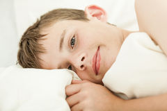 Close up of grinning boy in bed. Close up on face and hand of grinning brunette boy in bed with head on pillow and white blanket Royalty Free Stock Photo