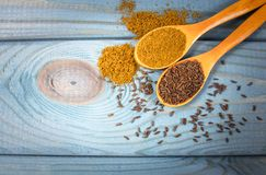 Ground cumin in a spoon and whole cumin on the wooden background. Close up on ground cumin in a spoon and whole cumin. Blue wooden background Royalty Free Stock Image