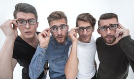 Close up. a group of creative friends looking at you through glasses. Stylized photo stock photography