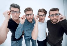 Close up. a group of creative friends looking at you through glasses. Stylized photo royalty free stock image