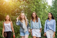 Four attractive young women talking walking together royalty free stock image