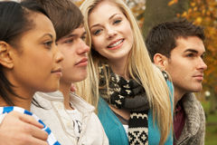 Close Up Of Group Of Four Teenage Friends. In Autumn Woodland Stock Photo