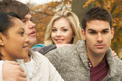 Close Up Of Group Of Four Teenage Friends. In Autumn Woodland Royalty Free Stock Photo