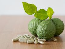 Close up group of fresh bergamot with green leaves and green capsule on wooden table. benefits of bergamot for beauty and health c Stock Image