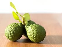 Close up group of fresh bergamot with green leaves on wooden table. benefits of bergamot for beauty and health concept. stock photos