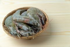 Close up group of fresh raw pacific white shrimp in bamboo bowl on wooden table royalty free stock photos
