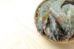 Close up group of fresh raw pacific white shrimp in bamboo bowl on wooden table royalty free stock image