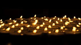 Lit candles in the dark. Close up of a group of lit candles in the dark stock video footage