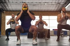 Multi-ethnic Group of Male Athletes Training in Crossfit Gym stock photo