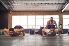 Close-up - Group of Male Muscular Friends Working Out in Gym.